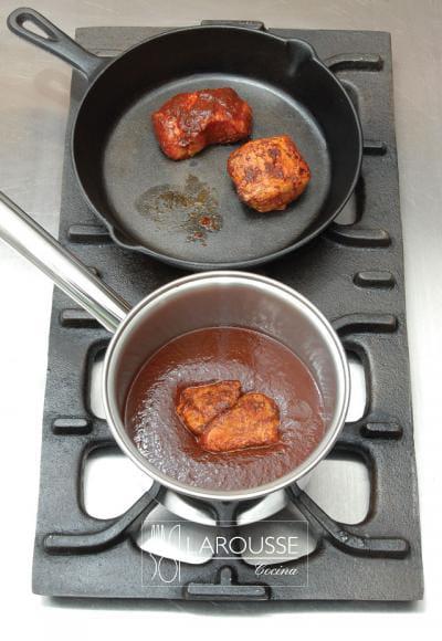 <p>Ponga sobre el fuego el resto del adobo, añadiendo suficiente líquido, de preferencia caldo, hasta obtener la consistencia de una salsa ligera. Agregue las piezas de carne.</p>