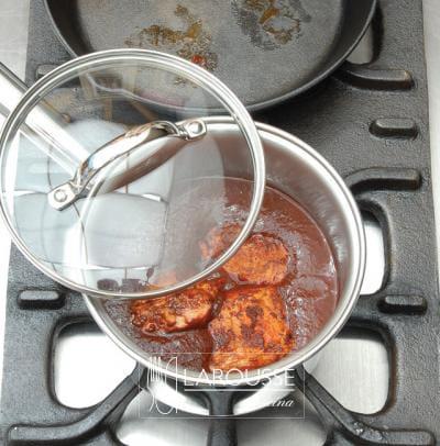 <p>Tape el recipiente y cocine el adobo a fuego bajo en la estufa, o dentro del horno a 180 ºC, hasta que la carne esté suave.</p>