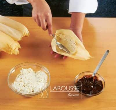 <p>Extienda la masa en el centro de una hoja de maíz o de elote.</p>