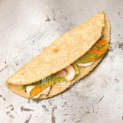 <p>Distribuya encima de la tortilla el relleno y ciérrela para formar la quesadilla. Déjela sobre el fuego hasta que la masa y el relleno estén cocidos.</p>