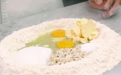 <p>Forme con la harina un círculo hueco sobre una mesa. Vacíeen el centro la levadura, 2 huevos, la margarina, la sal y elazúcar. Vierta un poco de leche e integre los ingredientesdel centro. Deje reposar la mezcla durante 5 minutos.</p>