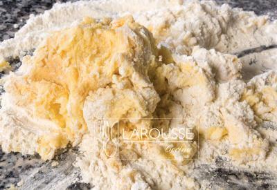 <p>Añadir la harina y trabajarla hastaobtener una consistencia granulosa. Amasarligeramente para obtener una masa.</p>