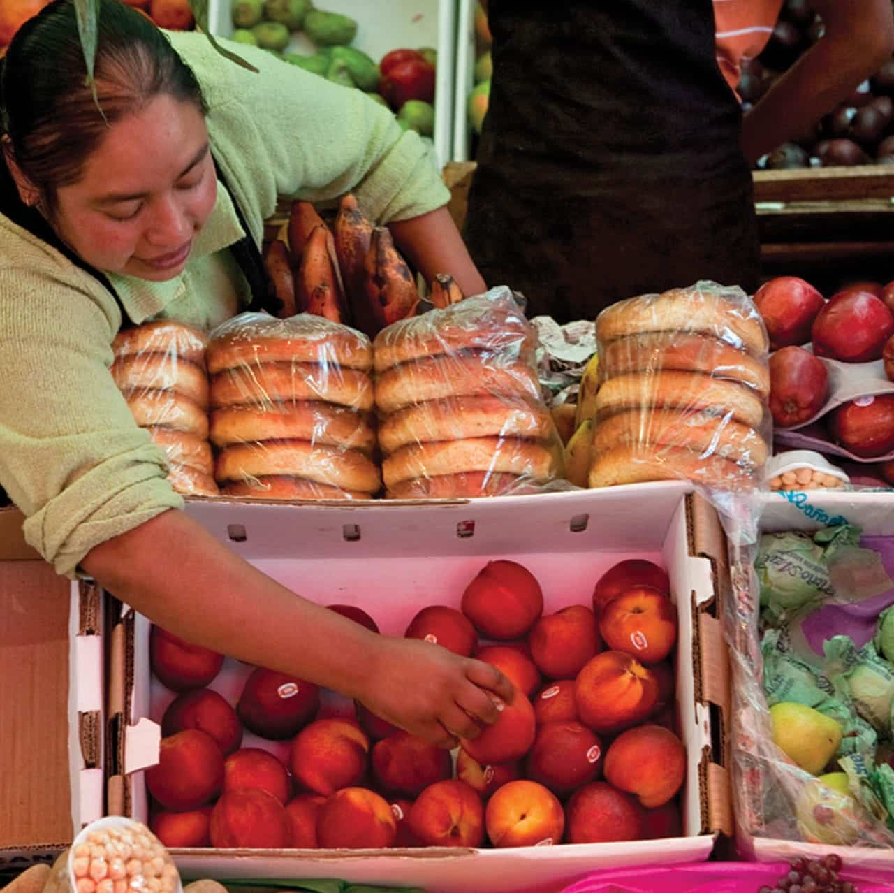 Foto: Mujer en puesto de fruta y pan. © Ediciones Larousse / Francisco Palma.