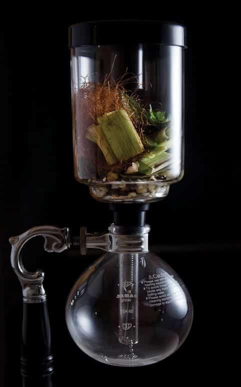 <p>Introduzca el caldo de maíz en cafeteras sifón o cona. Coloque en la parte superior el huitlacoche, los granos de maíz cocidos y tatemados, las hojas de epazote, el ajo y la cebolla tatemados, los 10 gramos de chile serrano, los pelos de elote, el totomoxtle quemado y la sal.</p>
