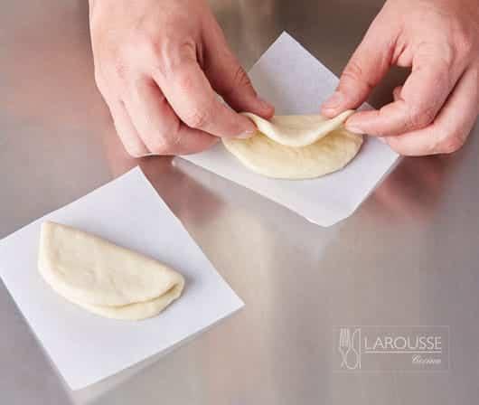 <p>Barnice la superficie de los discos de masa con un poco de aceite, dóblelos por la mitad sobre sí mismos y colóquelos sobre los cuadros de papel siliconado. Déjelos reposar cubiertos con una manta de cielo durante 10 minutos.</p>