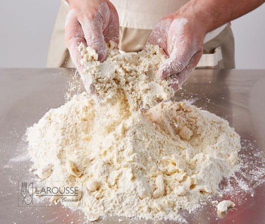 <p>Cierna sobre una superficie de trabajo la harina de trigo, la sal, el polvo para hornear y el azúcar. Añada los cubos de mantequilla e incorpórelos a la mezcla presionándolos con las yemas de los dedos hasta obtener una consistencia arenosa.</p>